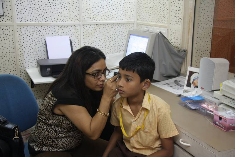 Audiologist Rupal peers into Omkar's ears during testing