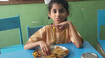 Child eating food at CSED